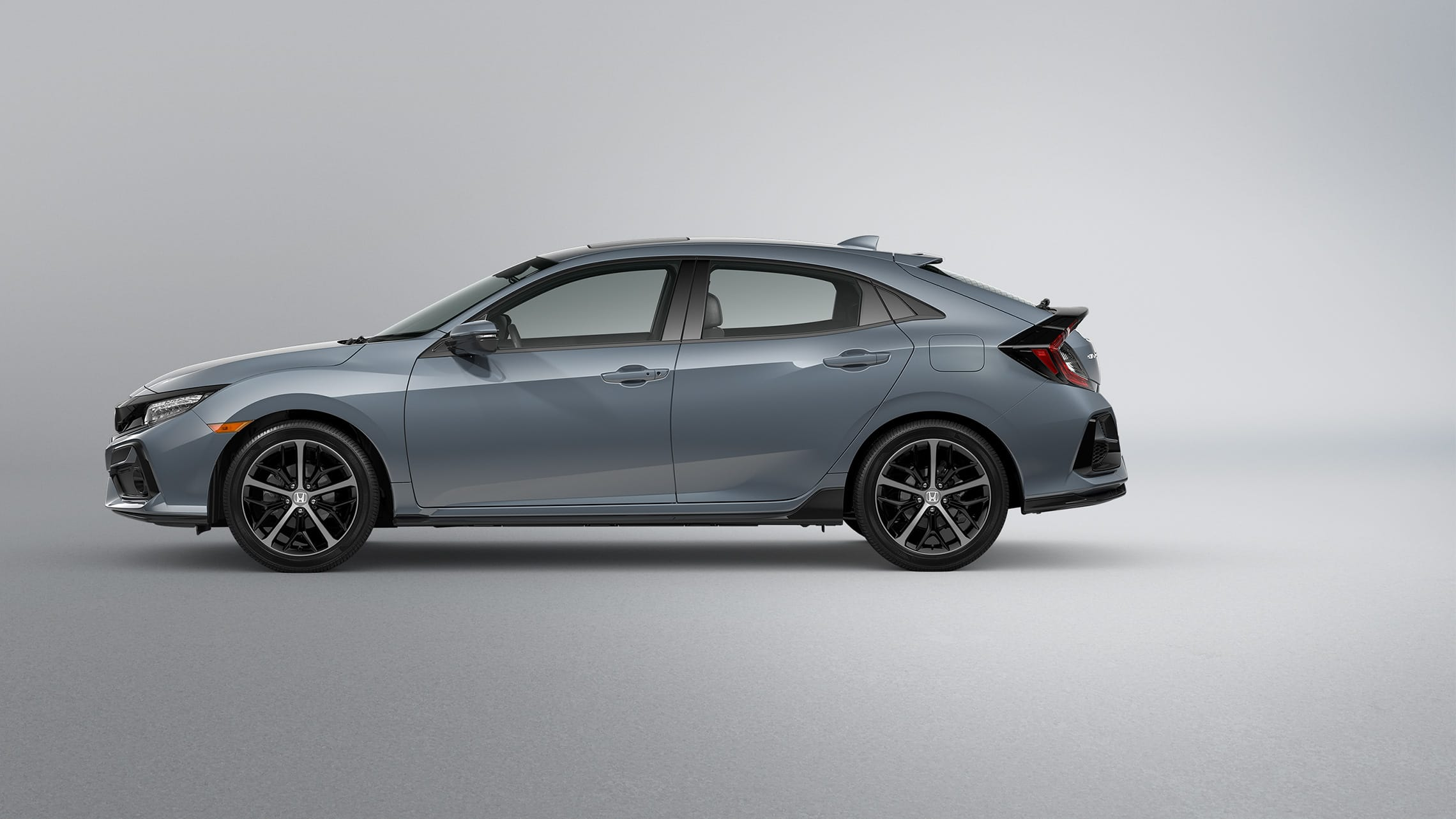 Driver-side profile view of the 2021 Honda Civic Sport Touring Hatchback in Sonic Gray Pearl.