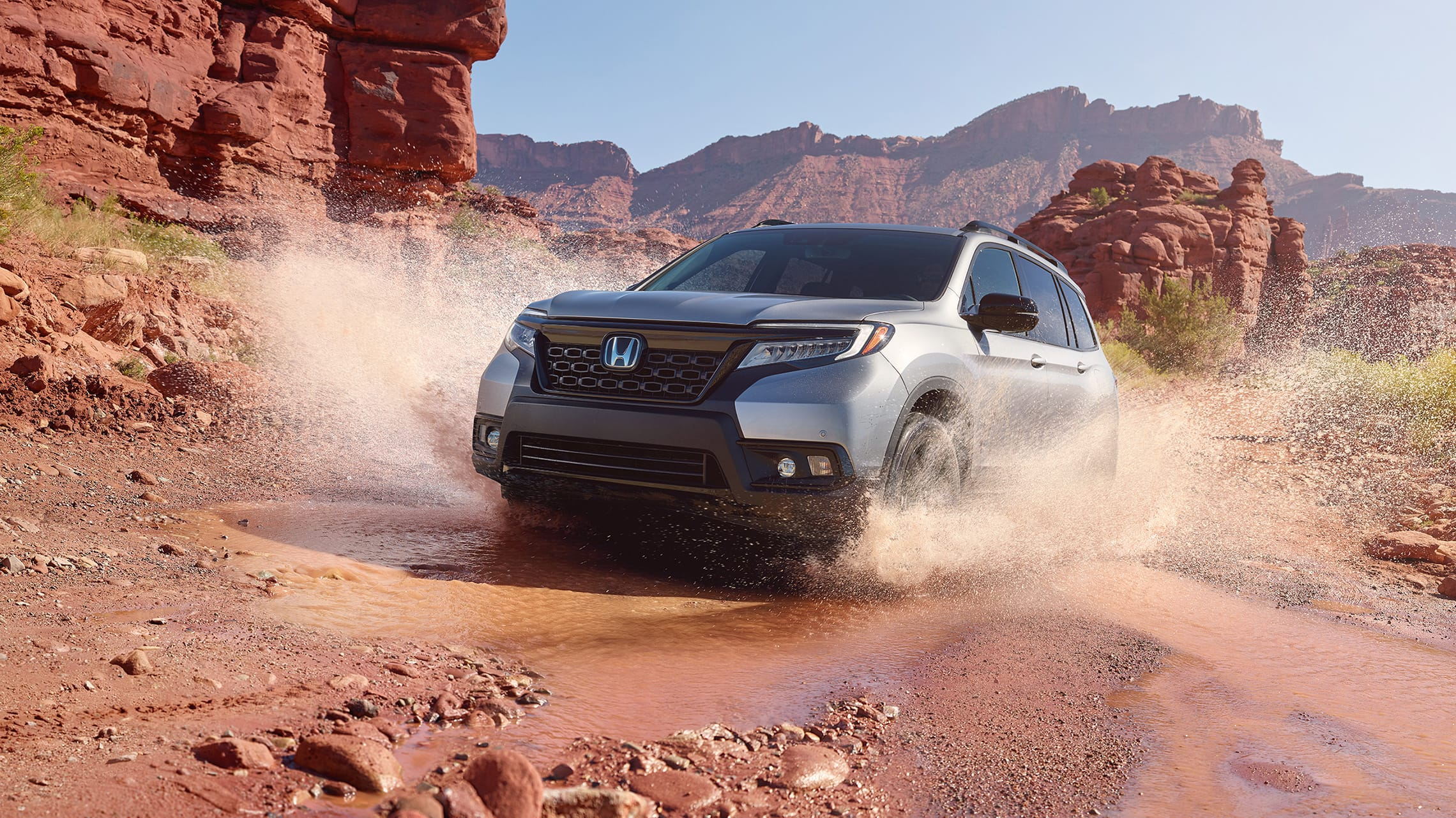 Driver-side front 3/4 view of 2020 Honda Passport Elite in Lunar Silver Metallic, demonstrating all-wheel drive and splashing through water on a rugged mountain road.