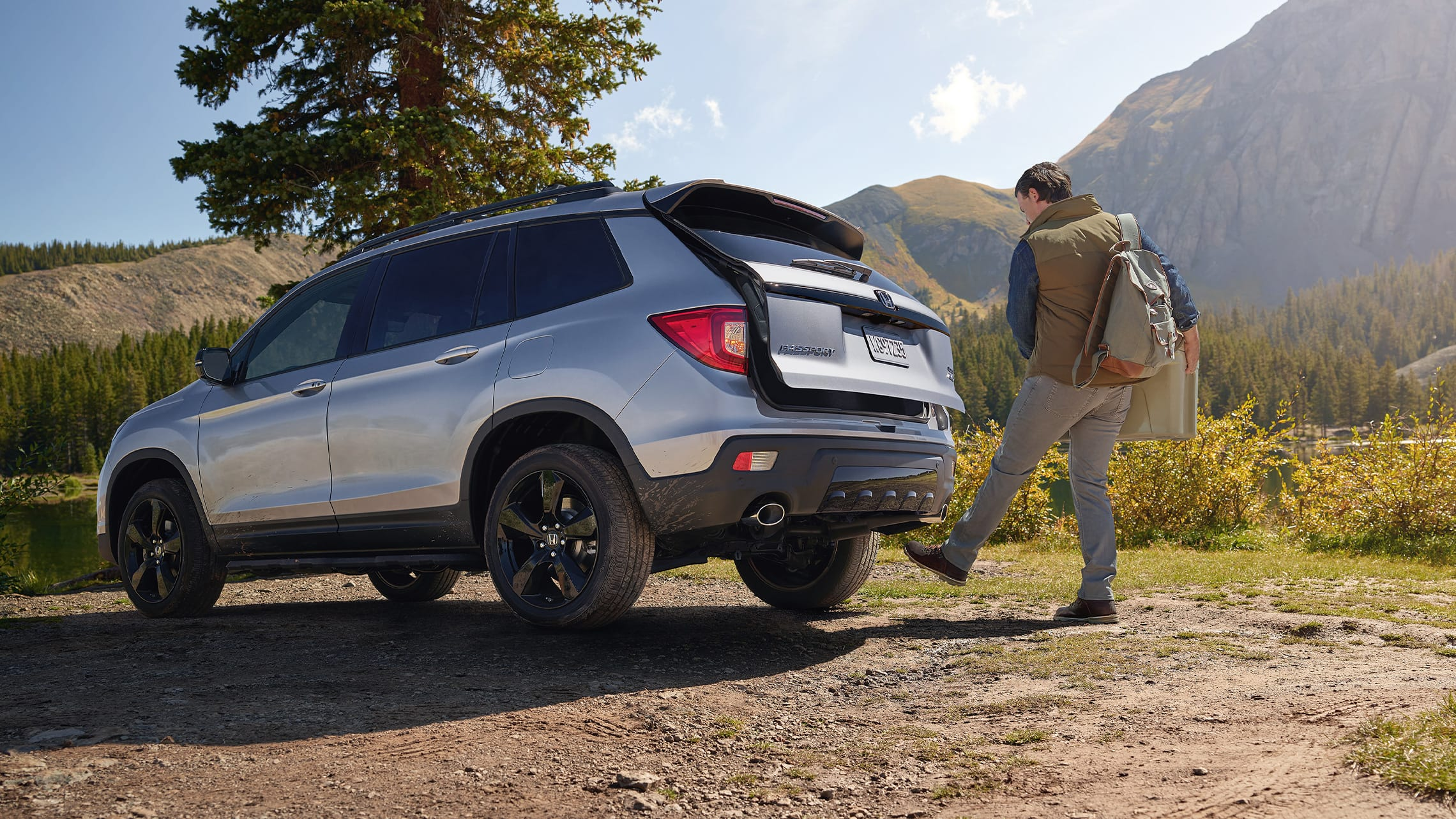 Driver-side rear view of the 2021 Honda Passport Elite in Lunar Silver Metallic, parked at campsite and demonstrating the hands-free access power tailgate feature.