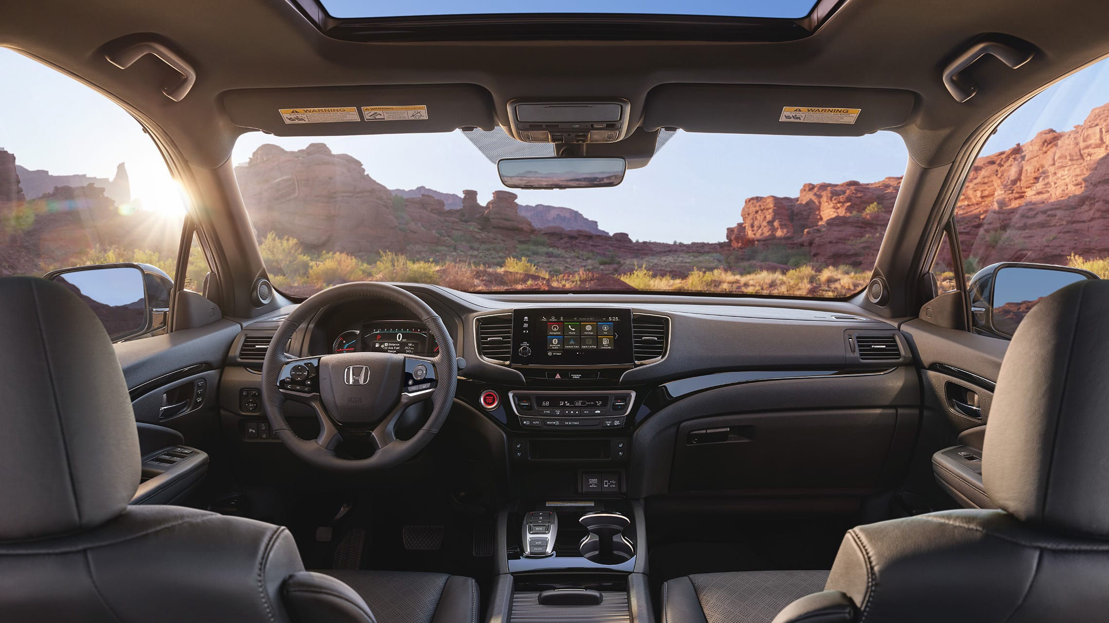 Interior view of the 2021 Honda Passport Elite with Black Leather showing the major instrument panel, featuring Apple CarPlay® integration on the Display Audio touch-screen.